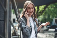 Cheerful young lady talking on the telephone near the banister stock images