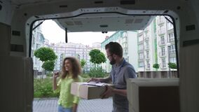 Cheerful lady giving cardboard box to courier for shipping
