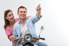 Cheerful young loving couple is driving motorbike royalty free stock photo