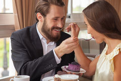 Cheerful young loving couple is eating sweet Royalty Free Stock Photos