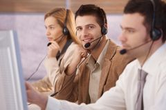 Cheerful young male dispatcher working. In callcenter, smiling Royalty Free Stock Image