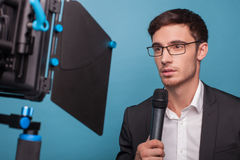 Cheerful young male journalist is reporting with Stock Images
