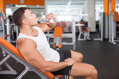 Cheerful young male sportsman is very thirsty Stock Photography