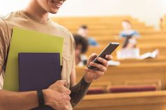 Happy guy typing message on smartphone in lecture hall. Cheerful young male student is using mobile phone at university. He is standing and smiling. Focus on Royalty Free Stock Photo