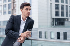 Cheerful young male worker is relaxing on break. Handsome businessman is standing near his office and leaning on the border. He is drinking coffee and relaxing Royalty Free Stock Photography