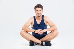 Cheerful young man athlete sitting with legs crossed Stock Photography