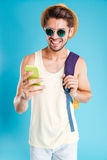 Cheerful young man with backpack using mobile phone. Cheerful young man in hat and sunglasses with backpack using mobile phone Royalty Free Stock Photo
