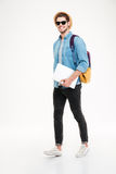 Cheerful young man with backpack walking and holding laptop royalty free stock photo