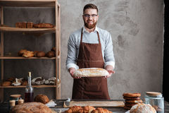 Cheerful young man baker standing at bakery holding bread. Image of cheerful young man baker standing at bakery holding bread. Looking at camera stock images