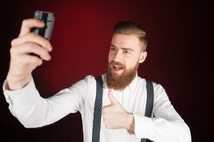 Cheerful young man with beard making selfie Stock Images