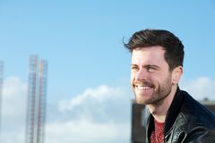 Cheerful young man with beard smiling outdoors. Close up portrait of a cheerful young man with beard smiling outdoors Royalty Free Stock Image