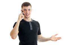 A cheerful young man in a black t-shirt said by mobile phone Royalty Free Stock Photos