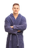 Cheerful young man in a blue bathrobe smiling royalty free stock photo