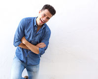 Cheerful young man in blue shirt laughing Stock Photos