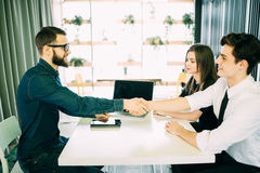 Cheerful young man bonding to his wife while shaking hand to man sitting in front of him at the desk Stock Image