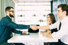 Cheerful young man bonding to his wife while shaking hand to man sitting in front of him at the desk Royalty Free Stock Images