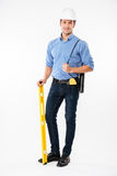 Cheerful young man builder in hard hat holding spirit level Stock Images