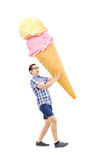 Cheerful young man carrying an enormous ice cream Stock Image