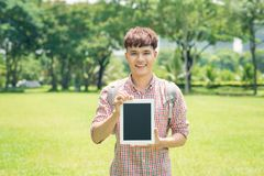 Cheerful young man in checkered shirt pointing on blank screen t Royalty Free Stock Photos