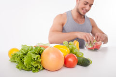Cheerful young man is cooking healthy food Stock Image