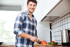 Cheerful young man cutting vegetables for salad on the kitchen Stock Photography