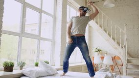 Cheerful young man dancing while getting experience using 360 VR headset glasses of virtual reality on bed at home. Cheerful young man dancing while getting royalty free stock image