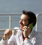Cheerful young man drinking coffee and talking on mobile phone. Close up portrait of a cheerful young man drinking coffee and talking on mobile phone Royalty Free Stock Image