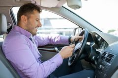 Cheerful young man is driving his transport Royalty Free Stock Images