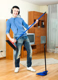 Cheerful young man  with dustpan and brush Royalty Free Stock Images