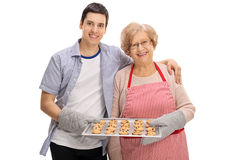 Cheerful young man and elderly lady holding tray of cookies royalty free stock photography
