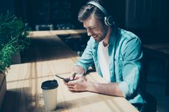 Cheerful young man enjoying listening to his favourite song at h. Is holiday in big white modern earphones, wearing casual outfit, sitting in a dark modern cafe Stock Photo