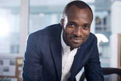 Cheerful young man is expressing gladness. Being successful. Portrait of pleasant happy young african businessman is looking at camera with joy while standing in stock photo