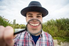 A cheerful young man holds a magnifying glass stock photography