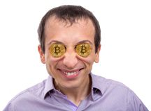 Cheerful young man with gold bitcoin in eyes stock photography