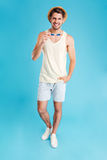 Cheerful young man in hat and shorts holding sunglasses Stock Photo