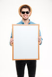Cheerful young man in hat and sunglasses holding blank whiteboard Royalty Free Stock Photo