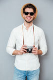 Cheerful young man in hat and sunglasses holding old camera Royalty Free Stock Photos