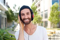 Cheerful young man with headphones outdoors Stock Photography
