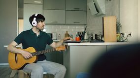 Cheerful young man with headphones sitting at kitchen learning to play guitar using laptop computer at home. Cheerful young man with headphones sitting at the Stock Photography