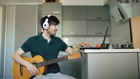 Cheerful young man with headphones sitting at kitchen learning to play guitar using laptop computer at home. Cheerful young man with headphones sitting at the Stock Images