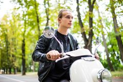 Cheerful young man in helmet is sitting on scooter and say hello while ride on city street. Royalty Free Stock Photo