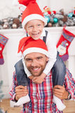 Cheerful young man and his child on Christmas. Handsome father and his son are celebrating New Year. The parent is holding his son on his shoulders. The boy is Royalty Free Stock Image