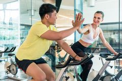 Cheerful young man and his workout partner giving high five during workout Royalty Free Stock Images