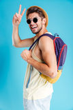 Cheerful young man holding backpack and showing peace sign Stock Photo
