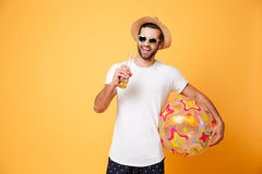 Cheerful young man holding beer and beach ball. Image of cheerful young man standing isolated over yellow background. Looking at camera holding beer and beach Royalty Free Stock Images