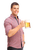 Cheerful young man holding a beer mug Royalty Free Stock Photos