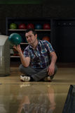 Cheerful Young Man Holding Bowling Ball Royalty Free Stock Photos