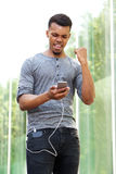 Cheerful young man holding cellphone Stock Photography