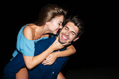 Cheerful young man holding girlfriend on his back at night. Cheerful attractive young men holding girlfriend on his back at night outdoors royalty free stock image