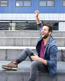 Cheerful young man holding mobile phone Stock Image